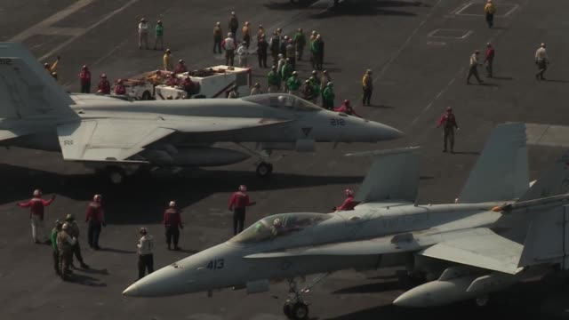 Sailors and Marines conduct flight operations aboard the aircraft carrier USS Nimitz