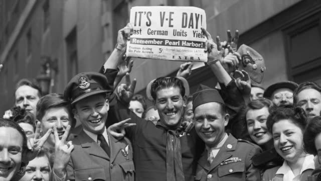 Sailors and soldiers celebrate Victory in Europe Day with a crowd in Times Square.