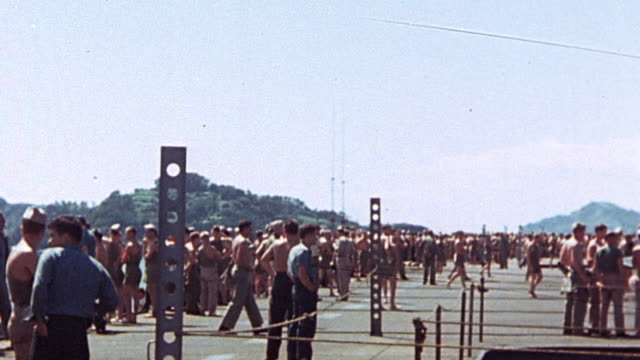 vidéos et rushes de sailors and soldiers lining the rails on deck of aircraft carrier getting underway mountains and other warships beyond / japan - vaisseau de guerre