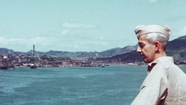 sailors and soldiers lining the rails on deck of anchored aircraft carrier mountains and other warships beyond american flag flying / japan - 1940~1949年点の映像素材/bロール