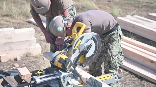 sailors assigned to naval mobile construction battalion work with ukranian marines in constructing a sentry post during exercise sea breeze 2019 in... - ドリルビット点の映像素材/bロール
