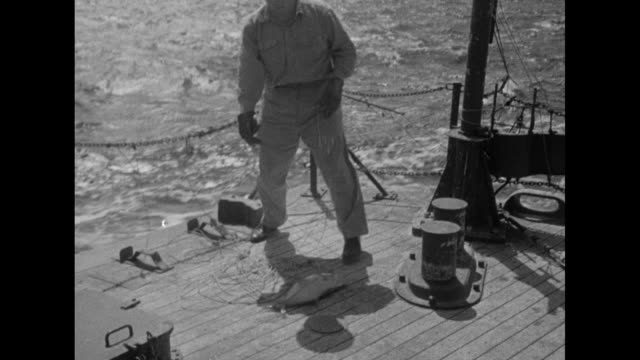 vídeos de stock e filmes b-roll de vs sailors at rear of ship use hand line to catch fish / vs fish in wooden box / vs one sailor records in book as another slices fish inserts piece... - atol de biquini