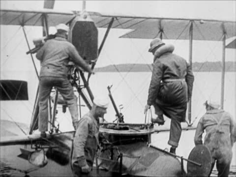 sailors cranking bi-plane out of hangar cranking. nc-4 : us navy men moving nc-4 airplane out of hangar us admiral shaking hands of crew nc-4 taxiing... - biplane stock videos & royalty-free footage