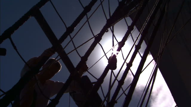 Sailors descend rigging on replica of HMS Endeavour.