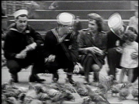 sailors english wac and small girl feeding pigeons / us army soldiers and english wac walking down busy street / sailors and wac getting directions... - matrose stock-videos und b-roll-filmmaterial
