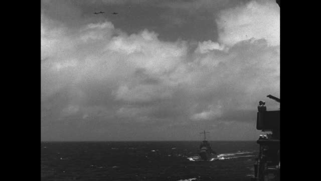 vidéos et rushes de sailors firing line of anti-aircraft guns on aircraft carrier for practice / various shots from carrier of planes flying in formation overhead /... - océan pacifique sud