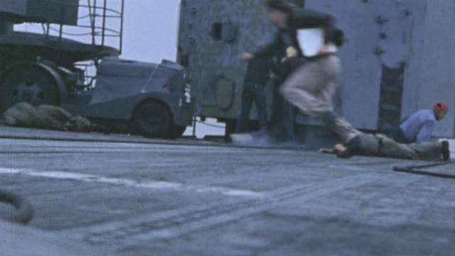 sailors fleeing across u.s. navy aircraft carrier flight deck, explosion off the starboard side, and burning japanese zero crashing into the sea... - pacific war video stock e b–roll
