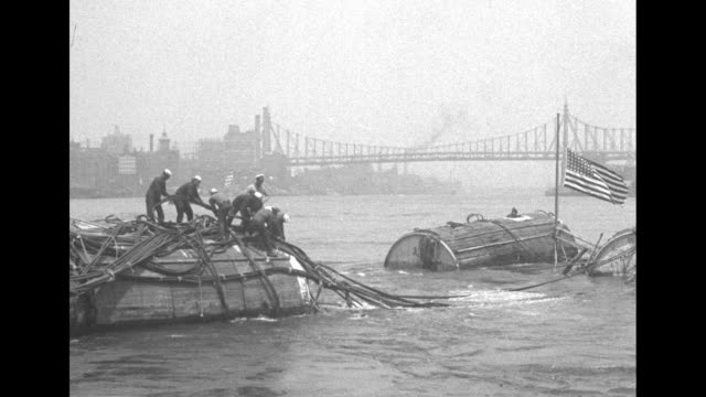 Sailors from salvage ship on top of barrels surrounding submerged but salvaged submarine the S51 which was sunk in October 1925 collision with SS...