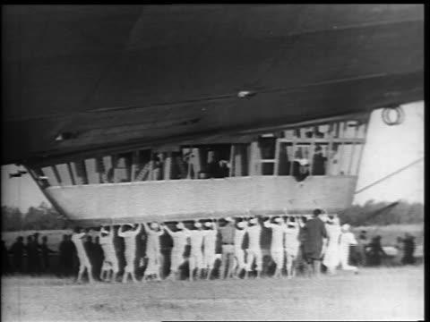 vidéos et rushes de b/w 1937 sailors holding gondola of hindenburg guiding it across ground / lakehurst nj - marinière