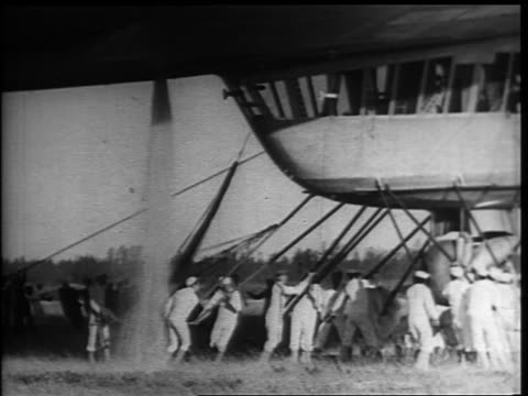 vidéos et rushes de b/w 1937 sailors holding onto gondola of docked hindenburg while water is being vented / new jersey - marinière