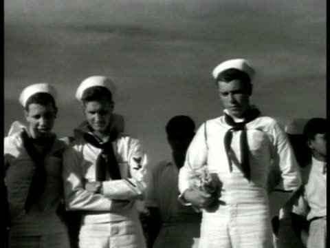 vidéos et rushes de sailors in 'dress whites' standing looking down indian male snake charmer playing instrument w/ two cobra snakes w/ heads raised on ground audience... - 1942