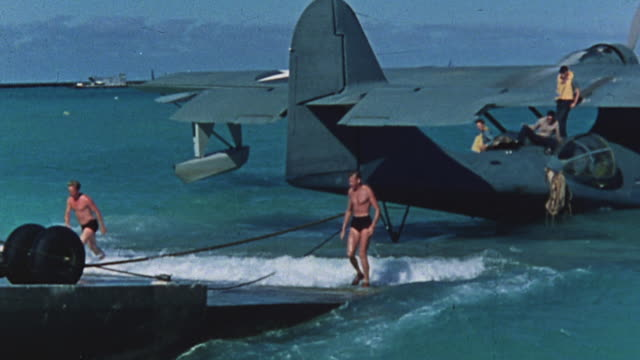 vídeos y material grabado en eventos de stock de sailors in swim suits pushing pby catalina onto loading ramp at island dock - bañador de hombre