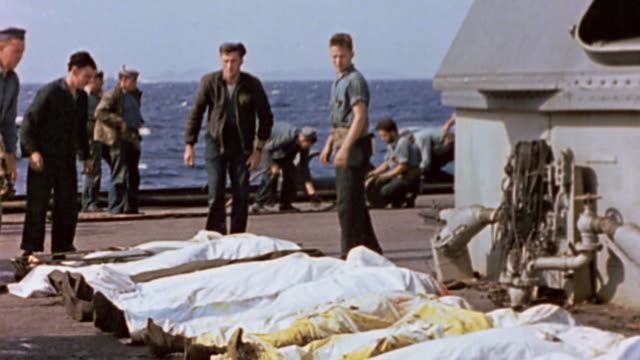 USN sailors laying casualties on deck and sewing them in after kamikaze attack