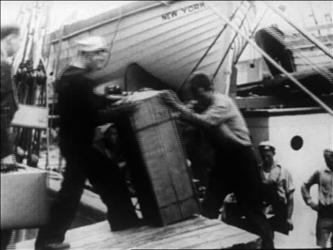 b/w 1926 sailors loading boxes on deck of admiral byrd's supply ship docked in ny harbor / newsreel - 1926 stock videos & royalty-free footage