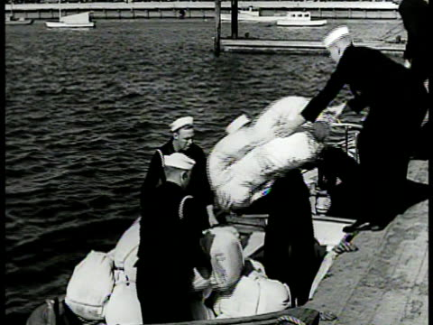 stockvideo's en b-roll-footage met sailors loading seabags on launch boat ws destroyer battleships in harbor launch boat passing fg ha ws sailors w/ bags boarding ship saluting to... - 1942