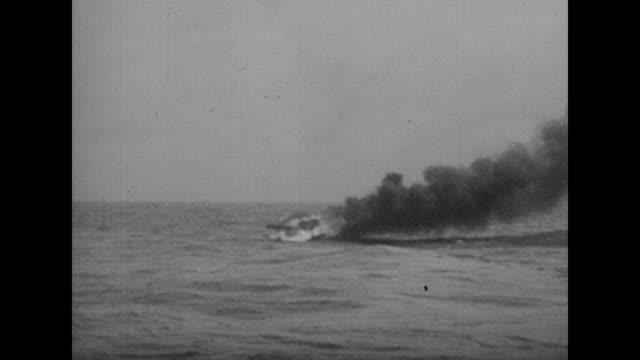 Sailors on submarine load shell into antiaircraft gun / two shots of sailor aiming gun / close view of gun firing / gun firing as cameraman shoots...