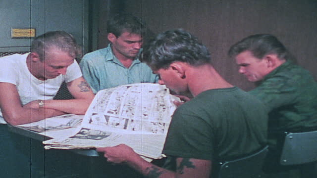 sailors playing cards writing letters and reading magazines at tables and in ship's bunk / vietnam - 刊行物点の映像素材/bロール