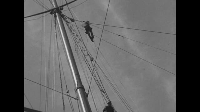 vídeos y material grabado en eventos de stock de sailors pushing heavy timber poles attached to circular turntable / men being slowly lowered from high mast to jagged rocks onshore / smaller boat... - devon