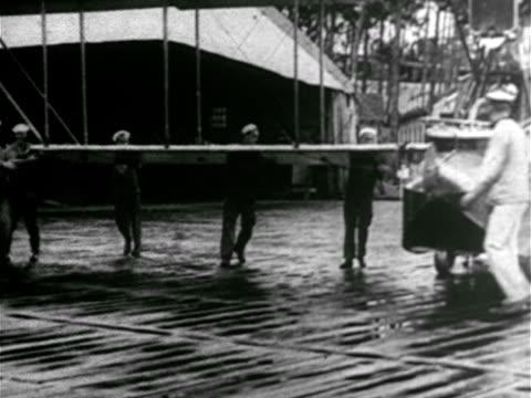 vídeos y material grabado en eventos de stock de sailors pushing hydroplane 'flying boat' out of hangar turning boat on dock pushing backward into water sailors loading bomb mounting machine gun... - hidroplano