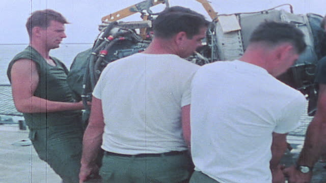 sailors repairing and testing helicopter aboard uss harnett county / vietnam - vietnam meridionale video stock e b–roll