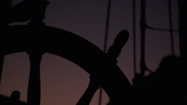 sailors silhouetted at the helm of the replica of hms endeavour. - 舵輪点の映像素材/bロール