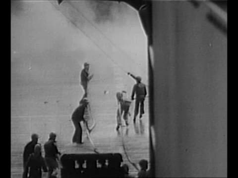 sailors spray water from hose at fire on deck of uss nevada which was hit by a japanese kamikaze plane during world war ii / montage sailors with... - 船の一部点の映像素材/bロール
