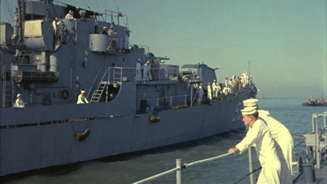 1967 MS Sailors standing on battleship, moving past another military ship