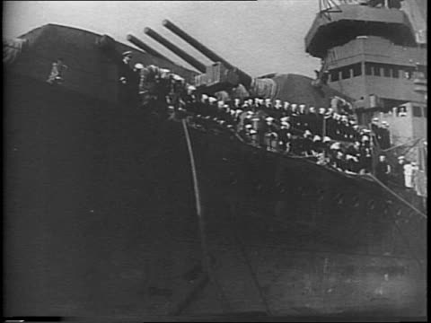 Sailors waving from the USS San Francisco / closeup of battered scars / boat pulling into pier pulling on ship's ropes / Mayor Angelo J Rossi in top...
