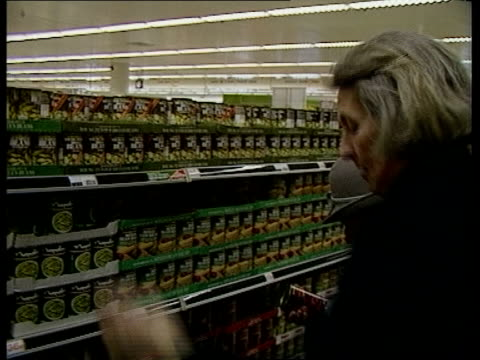 vídeos de stock e filmes b-roll de england london chiswick sainsburys ms shoppers with trolleys towards in aisle bv woman reaches for can of food off top shelf tms looks at can puts... - sainsburys