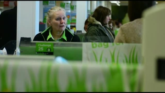 vídeos de stock e filmes b-roll de sainsbury's confirms planned merger with asda england london nine elms int customer packing plastic bags at sainsbury's supermarket checkout woman... - sainsburys