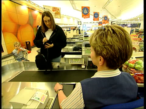 Sainsbury's Jobs axed after poor profit rise ENGLAND London Woman at checkout in Sainsbury's supermarket
