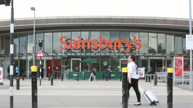 vídeos de stock e filmes b-roll de sainsburys logos sit on the handles of shopping carts as they stand outside the entrance to one of the companys supermarket stores operated by j... - sainsburys