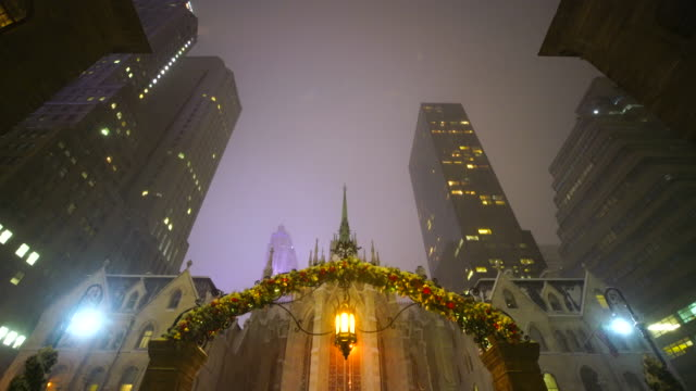 saint patrick's cathedral and skyscrapers in snow night at midtown manhattan. the gate at front is in new york palace hotel, which is decorated by christmas decoration. - st. patrick's cathedral manhattan stock videos and b-roll footage