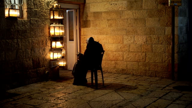 a saintly woman reads psalms by the light of the menorah in the rova jewish quarter of the old city - psalms stock videos and b-roll footage