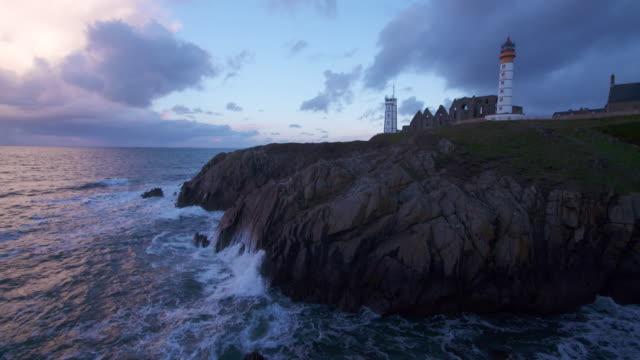 Saint-Mathieu lighthouse (Pointe Saint-Mathieu) at rocky coastline short after sunrise.