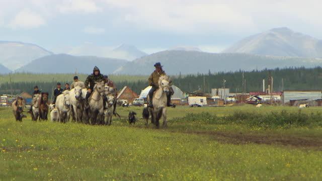sakha horsemen ride through the village of sakkyryr. - cowboy stock videos & royalty-free footage
