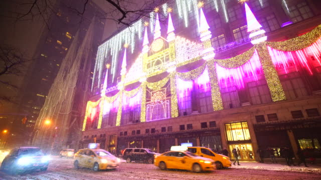 2016 Saks Fifth Avenue Holiday Light Show during the snow at night in Midtown Manhattan. Exterior of Saks Fifth Avenue and window displays are decorated for Christmas decoration. Cars run on Snow covered 5th Avenue.