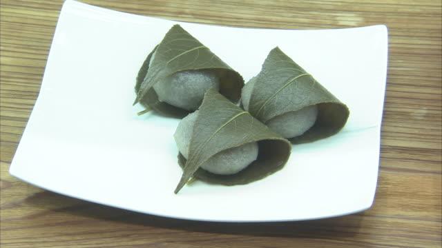 vídeos y material grabado en eventos de stock de cu sakuramochi on plate, tokyo, japan - cuatro objetos