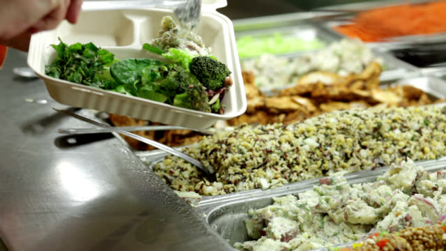 salad bar customer fills to-go container. - utensil stock videos & royalty-free footage