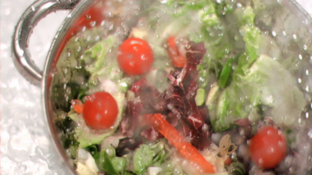 Salad being washed in super slow motion
