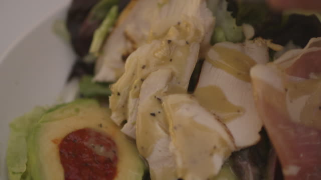salad dressing is drizzled over a chicken, ham and avocado salad, uk. - salad dressing stock videos & royalty-free footage