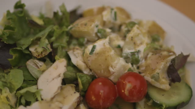 salad dressing is poured over a potato, chicken and cherry tomato salad, uk. - salad dressing stock videos & royalty-free footage