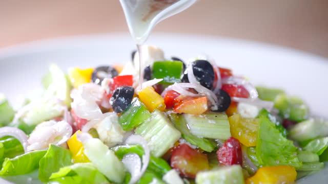 ミックスグリーンサラダ1皿に注がれたslo moサラダドレッシング - サラダドレッシング点の映像素材/bロール