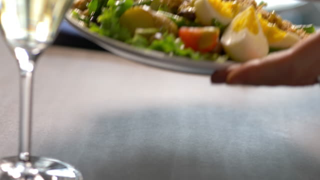 salad nicoise presented at table with wine glass in foreground - salad nicoise stock videos & royalty-free footage