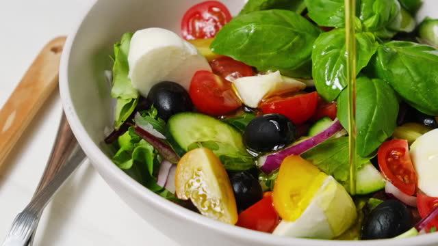 salad with mozzarella cheese, tomatoes, arugula, black olives and olive oil, healthy food - 義大利文化 個影片檔及 b 捲影像