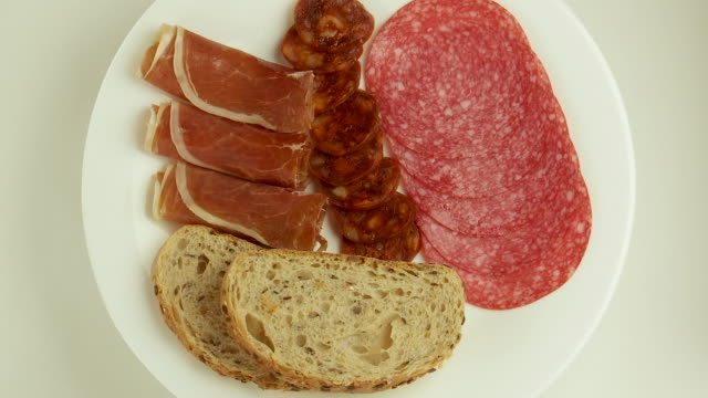 salami,ham,chorizo,bread slices on white revolving plate - chorizo stock videos & royalty-free footage
