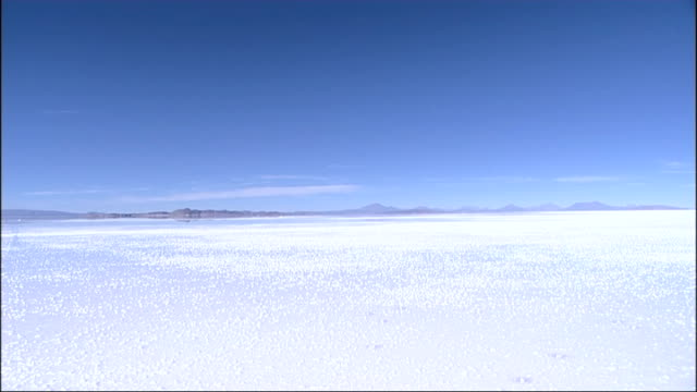 salar de uyuni salt flats: general views / lithium research; tracking shot from moving car as drives through wet salt flats / back view jeep driving... - evaporation stock videos & royalty-free footage