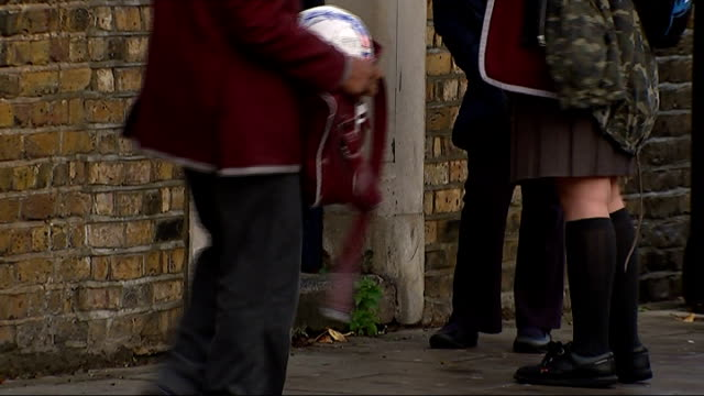Salary of Academy headteacher sparks nationwide review London Stockwell EXT Durand Academy school Feet of children through gates Reporter to camera
