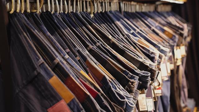 verkauf sortiment denim-kollektionsstand im boutique-shop - jeans stock-videos und b-roll-filmmaterial