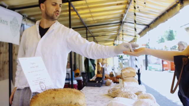 sale at sunny outdoor market - bancarella video stock e b–roll